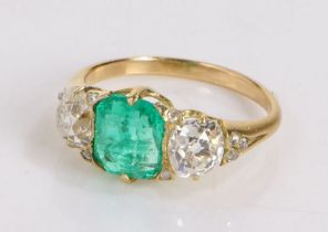 Emerald and diamond set gold ring, the central 1.7ct emerald flanked by two 0.85ct diamonds, ring