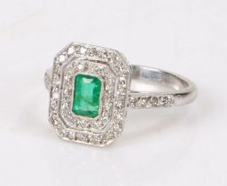18 carat white gold diamond and emerald set ring, the central emerald at an estimated 0.44 carat and