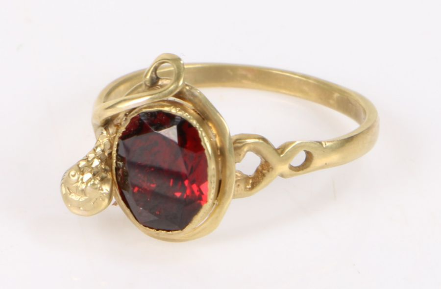19th Century garnet set ring, the oval garnet with a coiled snake to the side, gross weight 2.3