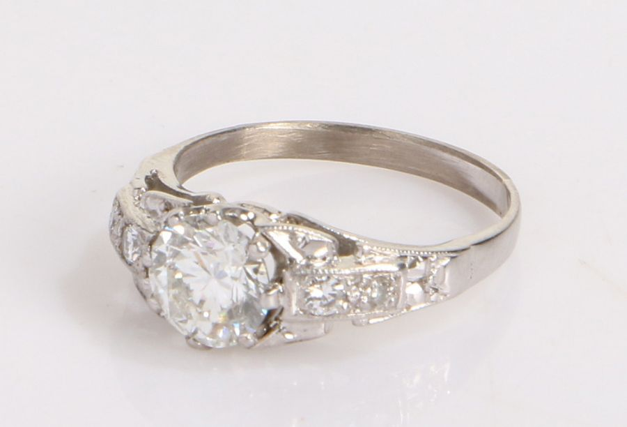 Diamond ring, the central 1.03ct diamond flanked by shaped diamond set shoulders, ring size J 1/2,