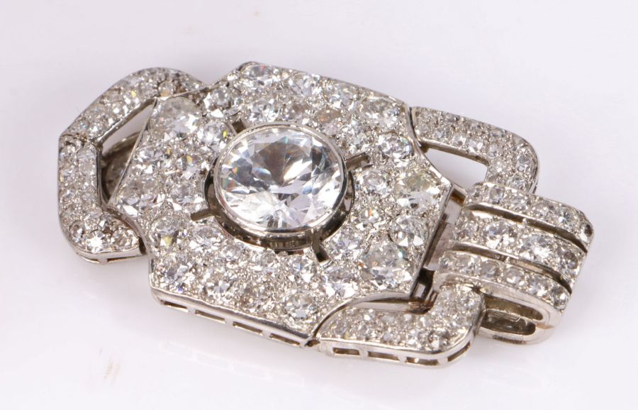 An impressive Art Deco diamond and white sapphire clasp, the central white sapphire at an