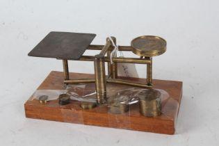 Set of 20th century brass scales, raised on oak base, 18cm wide