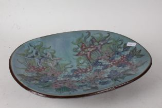 Chelsea Pottery, a large shallow dish, decorated flowers on a turquoise ground, raised on four feet,