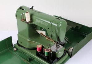 Elna sewing machine, in green, housed within a metal carrying case (sold as collectors item)