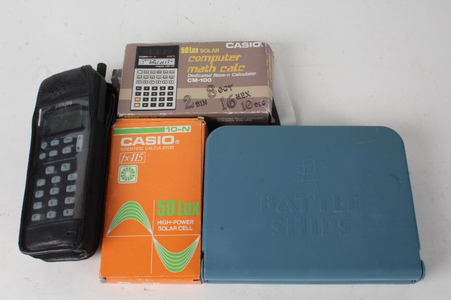 Casio fx-115 boxed calculator, Philips PR143 mobile phone, Casio CM-100 boxed calculator, and a