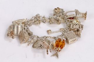 Silver charm bracelet, to include three pence piece, Canadian five cents and various other charms