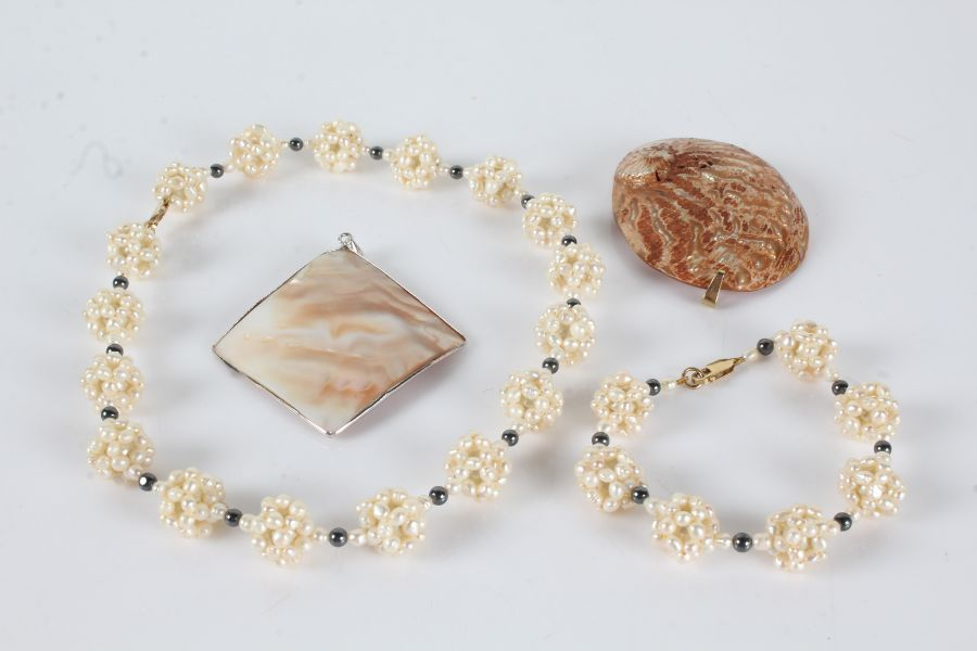 Simulated pearl necklace and bracelet together with pendant formed out of a sea shell and another