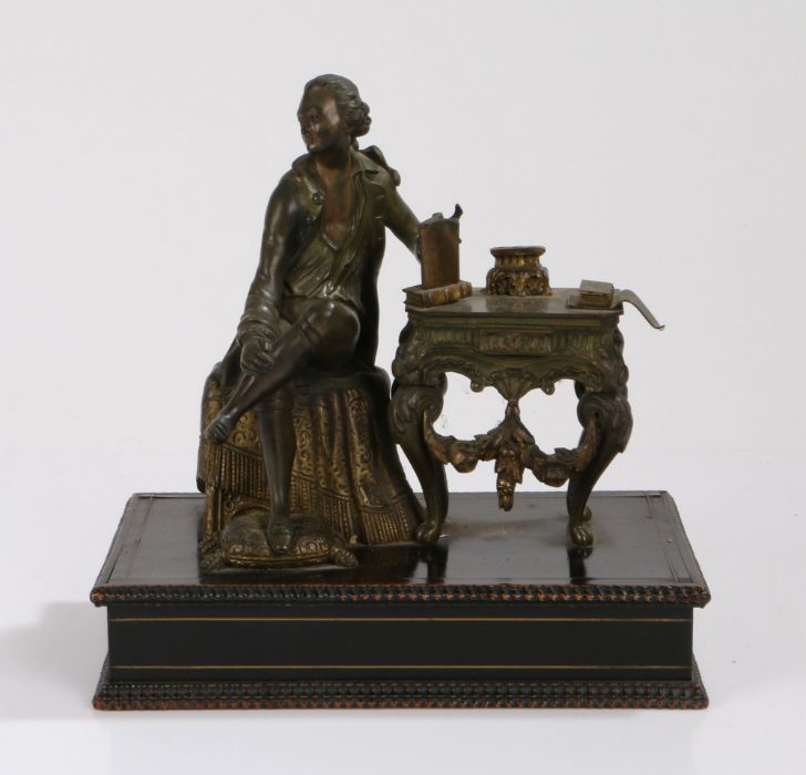 Bronze figure, of a gentleman seated on table with a draped cloth, his foot rested on a cushion,