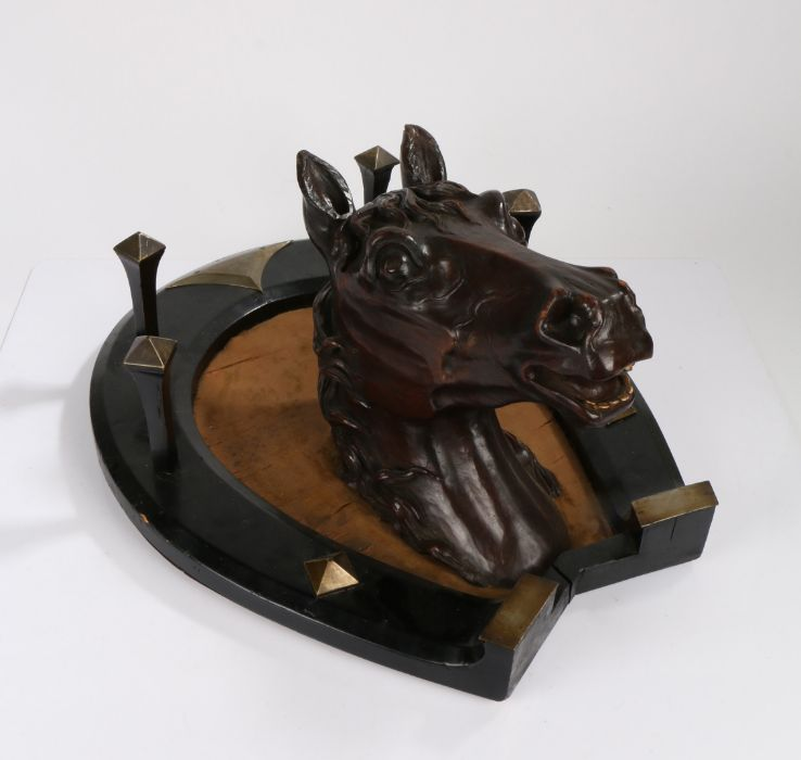 Victorian carved wooden horses head, mounted to an ebonised and metal mounted horseshoe with four