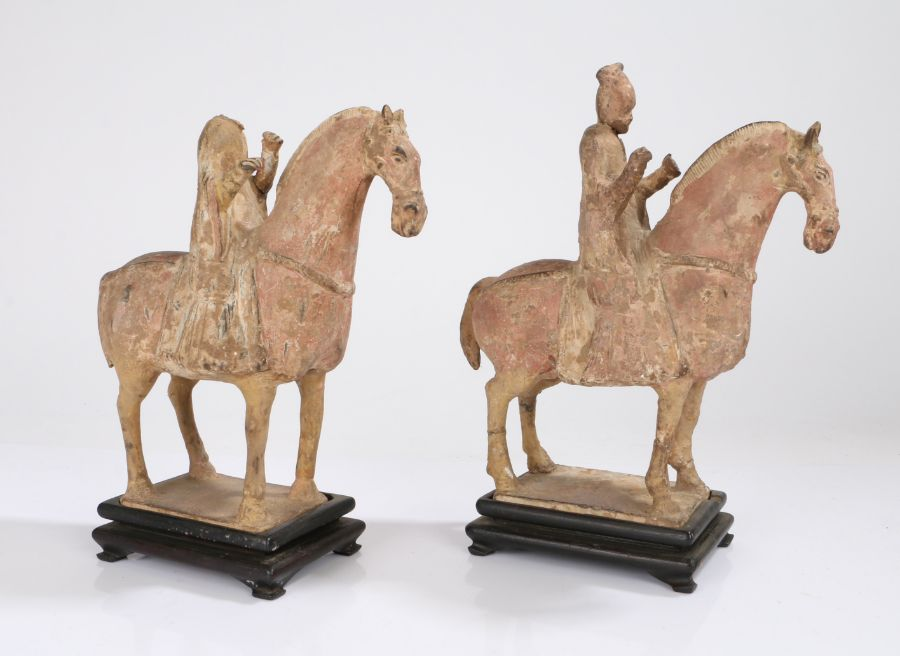 Near pair of Chinese pottery horse and riders, Tang Dynasty, with pale red painted bodies with