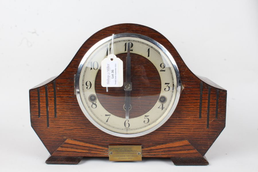 Art Deco style oak mantel clock, the arched case with engraved line decoration and brass