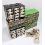 Four plastic and metal banks of workshop drawers, containing watch batteries, crowns, hands etc. (