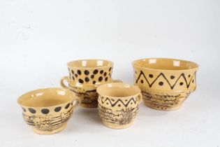 20th Century pottery slipware, to include a porringer, another and two cups, (4)