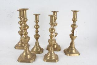 Three pairs of 19th century brass candlesticks, each of the same form with knopped columns and