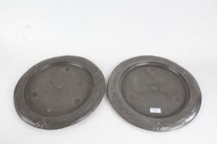 Pair of Art Nouveau pewter chargers, with foliate and scroll decorated central fields and borders,