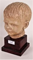 Art Deco style pottery bust, in the form of a boy, raised on a marble effect plinth, 23.5cm high