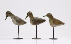 A trio of early 20th Century Shorebird decoys, the painted body with red bead eyes raised on later