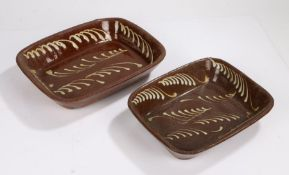 Two pottery slipware baking dishes, both of rectangular form and high sides decorated with wriggle