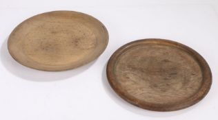 Two 19th Centurytreen platters, the first in oak with a rounded edge, 29cm wide, the second in