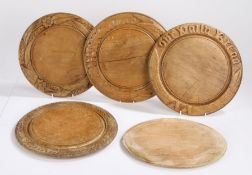 Collection of five treen breadboards, the first with the text Our Daily Bread, 29cm wide, another