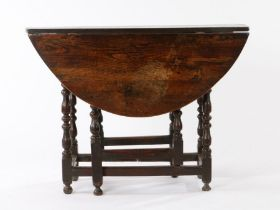 Mid 17th Century oak gateleg table, the oval drop leaf top above a moulded frieze and turned legs,