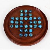 Mahogany solitaire board, with thirty-two glass marbles with blue swirls, the base bearing label for