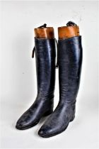 Pair of black leather riding boots, with wooden boot trees bearing label 'Arthur E. Jordan Bootmaker