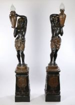 Pair of Egyptian revival metal torchere's, the figural lamps with an Egyptian figure holding a