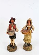 Two pottery figures, of a bearded man and a lady holding a basket of flowers, stamped to the bases