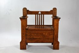Arts and Crafts oak hall seat, having stick stand divisions either side of a storage seat, with