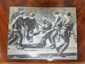 LARGE 1970'S PHOTOGRAPH OF INJURED BRITISH SOLDIER ON LOWER FALLS ROAD