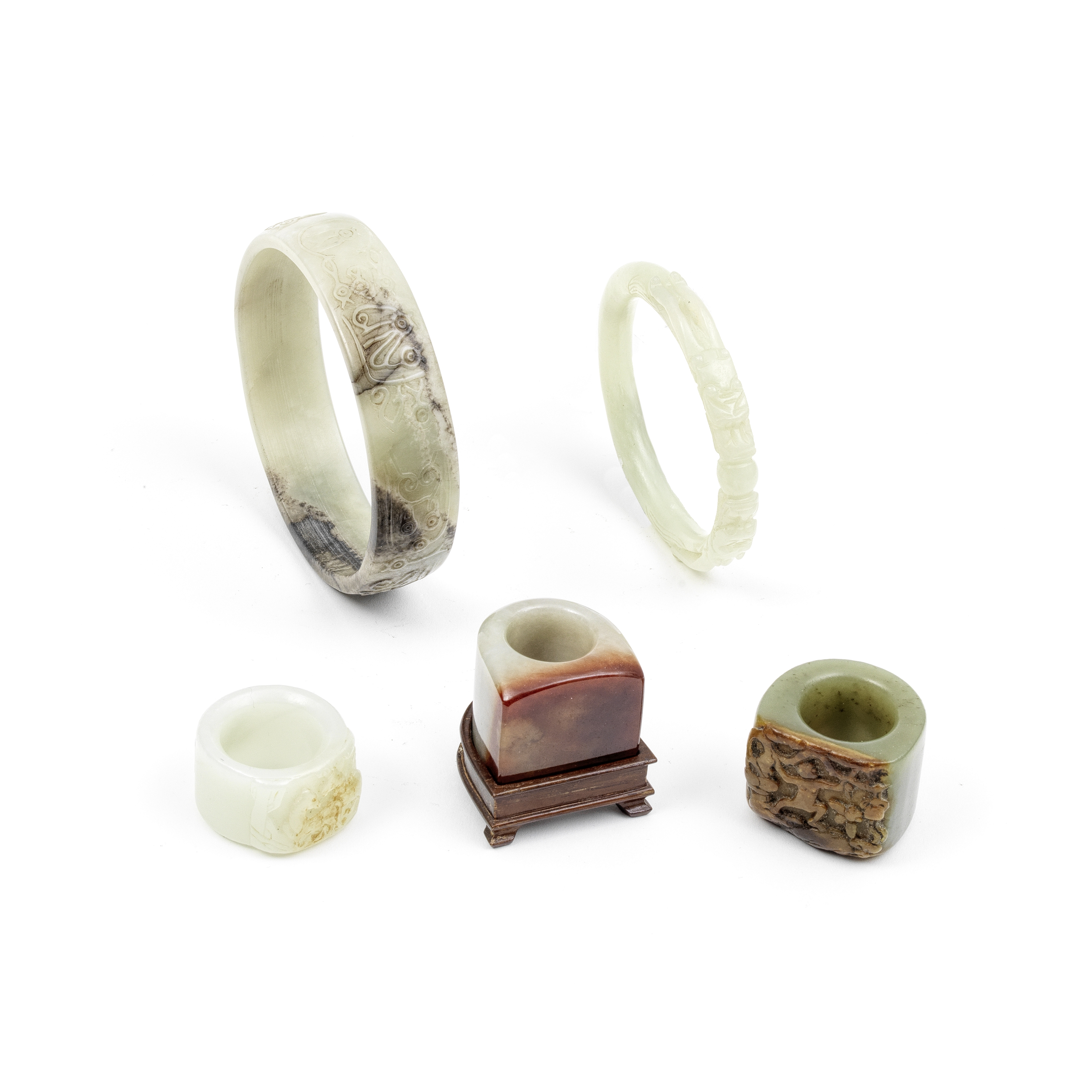 A GROUP OF VARIOUSLY JADE, JADEITE, AND HARDSTONE BANGLES AND THUMB RINGS Qing Dynasty and later (6)