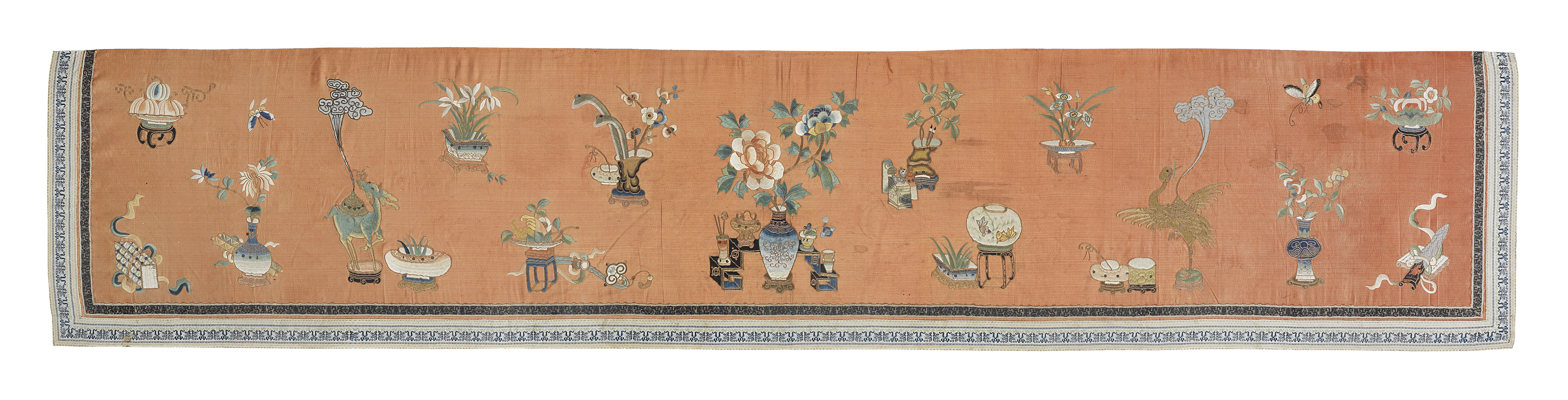 AN APRICOT-GROUND SILK-EMBROIDERED 'HUNDRED ANTIQUES' TEXTILE Late Qing Dynasty