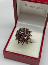 A Ladies silver and garnet cluster ring. [Ring size M]