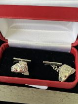 A Pair of silver salmon headed cufflinks with ruby eyes.