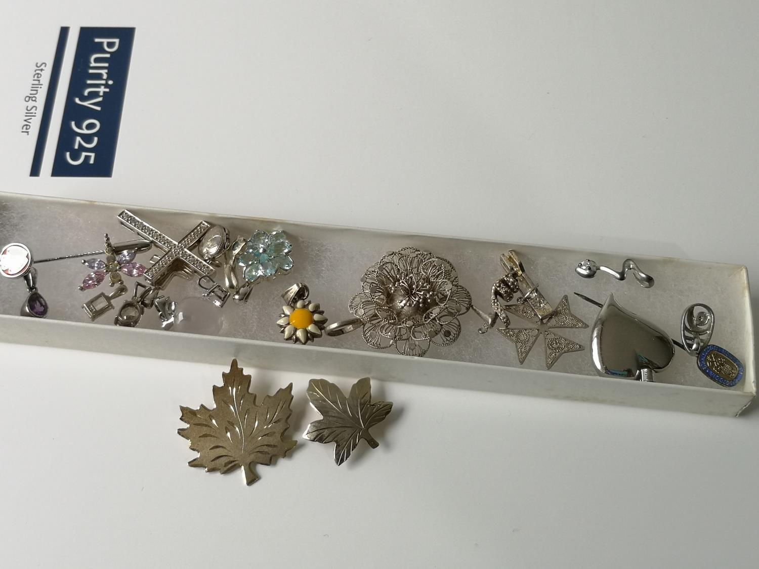 A Collection of silver marked brooches, charms and pendants.