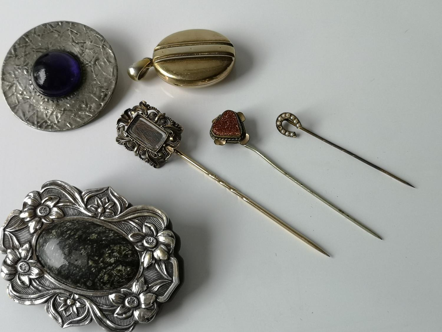 A Lot of three antique hat pins, gilt metal locket, arts & crafts blue stone brooch & a plated
