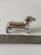 A Silver sausage dog figure. [3.8cm in length]