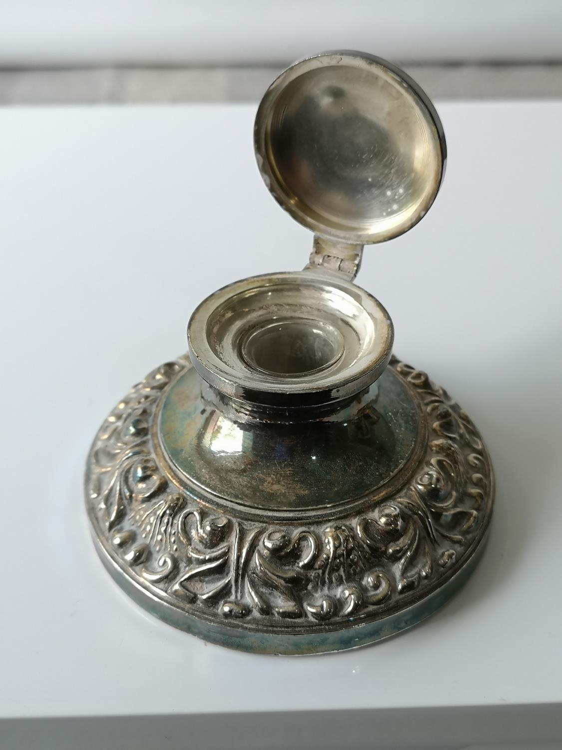 An antique ornate white metal/ plated ink well pot with glass insert. [5.5x9.5x9.5cm]