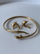 A 9ct gold dolphin design bangle, together with a pair of dolphin earrings [6cm] [7.51g]