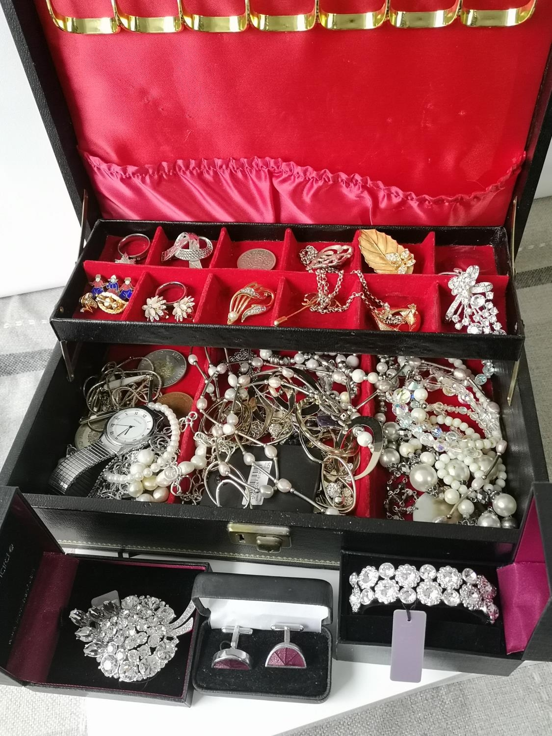 A Jewellery box containing a quantity of costume jewellery to include brooches, necklaces,