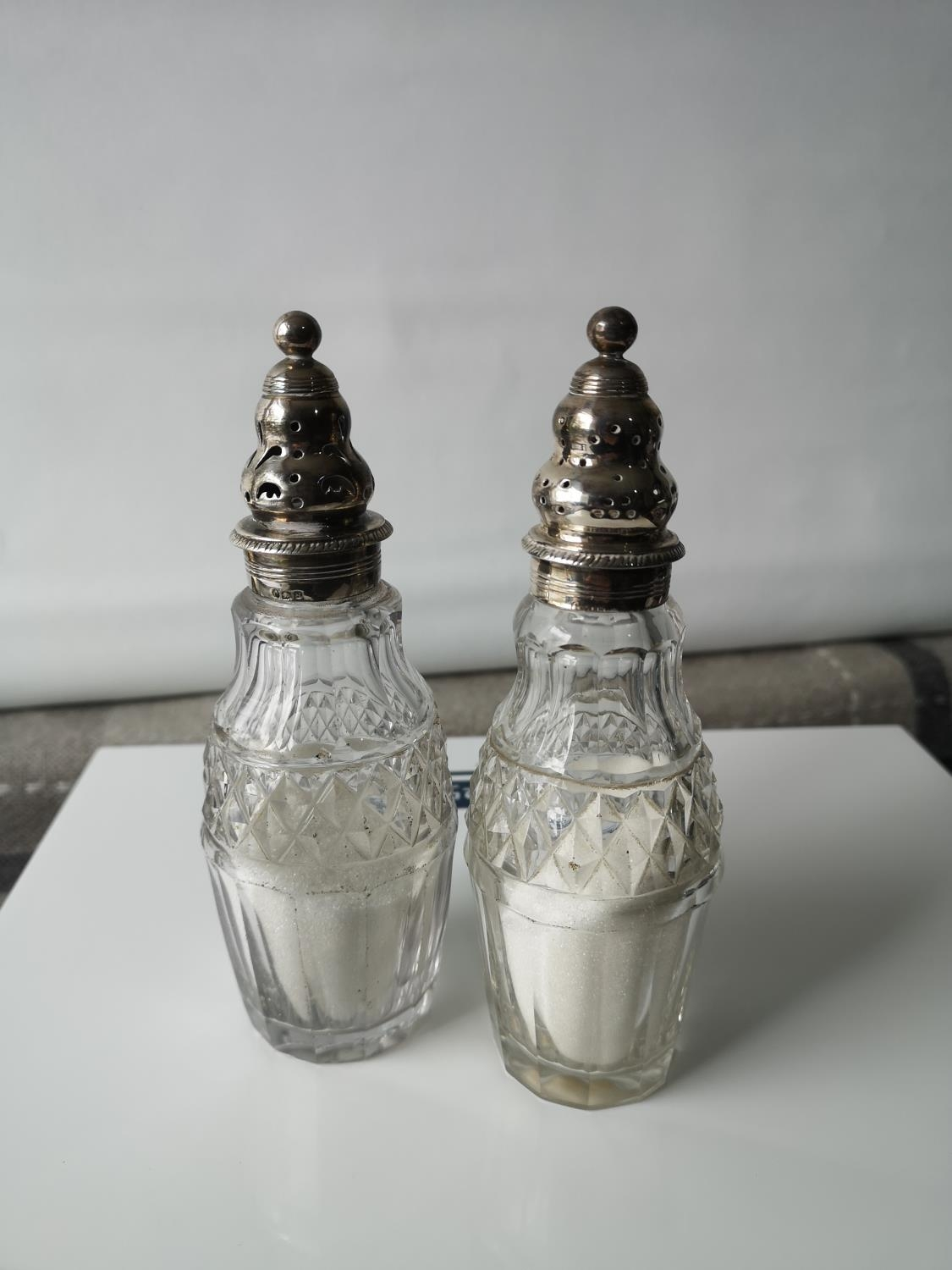 Two silver top & glass body sugar shakers [16cm in height]