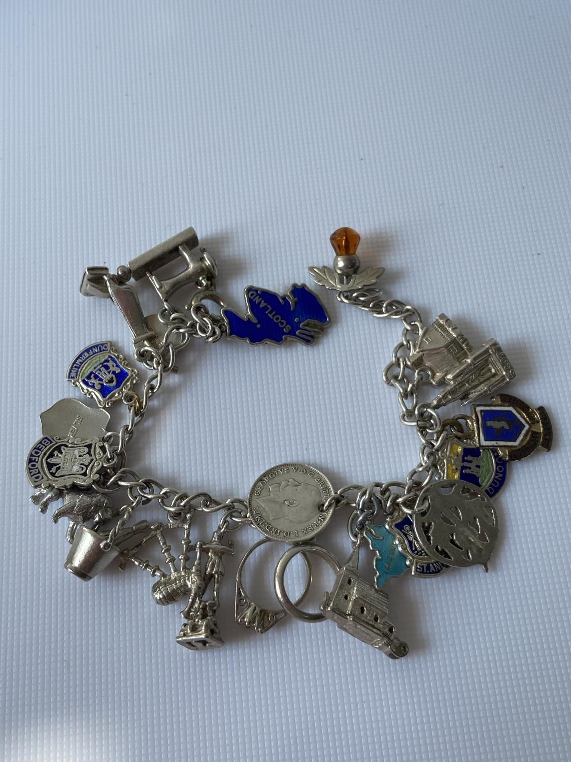 A silver charm bracelet fitted with 23 various silver chains, includes silver & enamel charms [