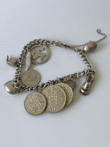 A white metal charm bracelet set with various silver charms