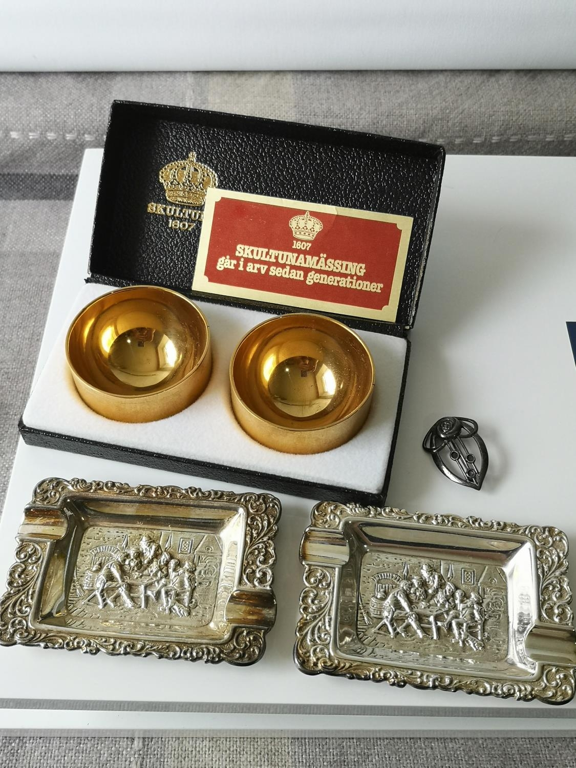 A Pair of boxed gold plated Swedish Skultuna cruet pots together with two ornate silver plated ash