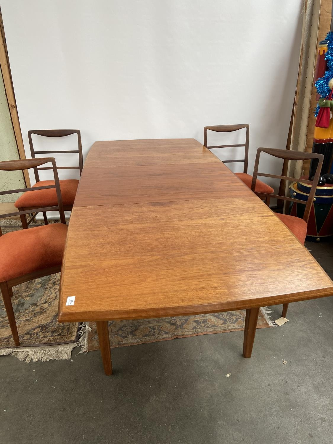 A Retro mid century teak dining table and four matching chairs produced by Vanson. [Table extended