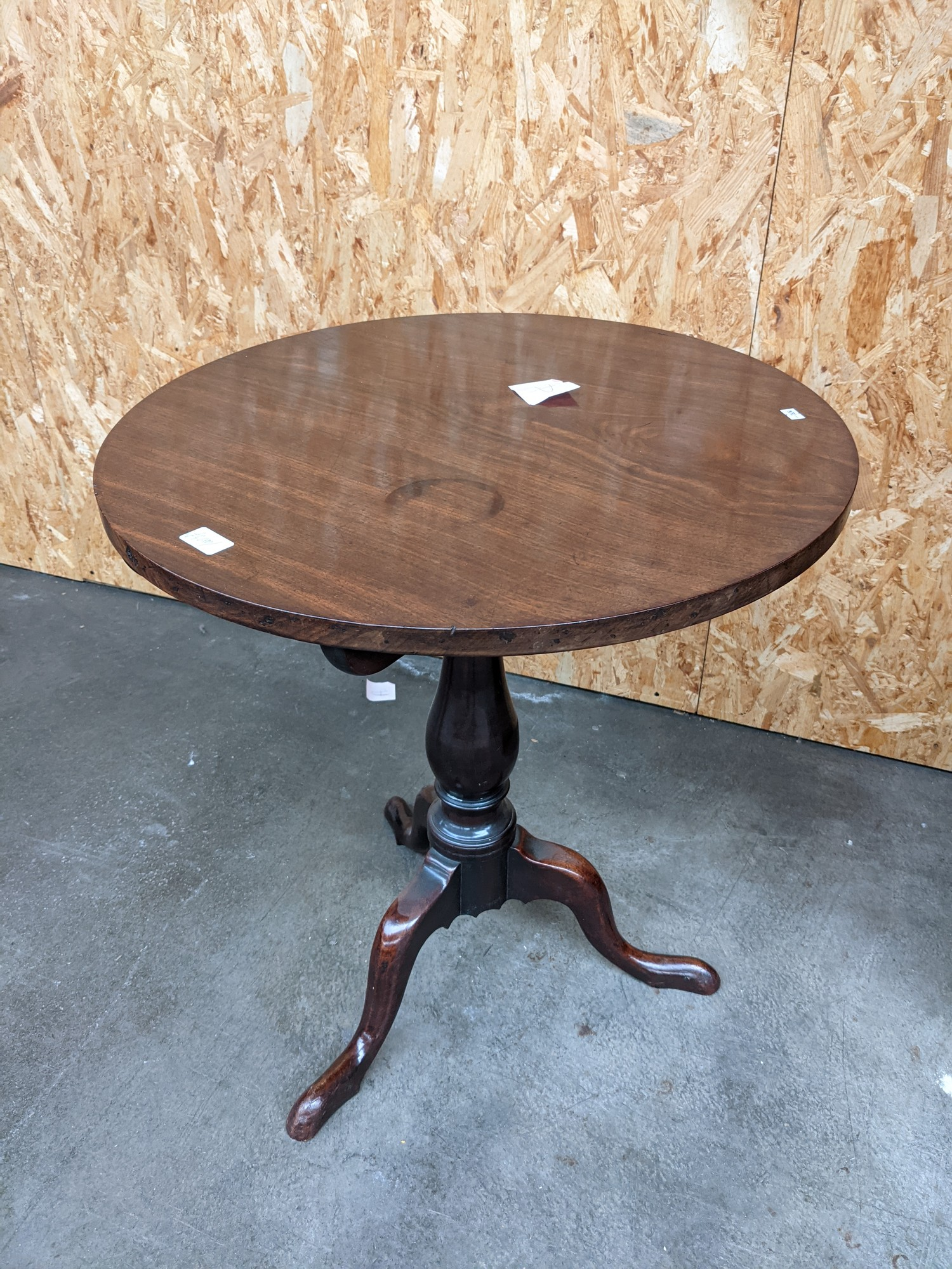 A mahogany circular flip top table supported on a tri leg [height, 67cm, diameter, 61cm]