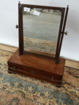 A Georgian adjustable dressing mirror upon a one drawer concave base, on bracket feet