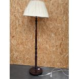 A mahogany free standing lamp, on a circular base, with shade [height with shade, 1.7m]