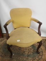 A Victorian arm chair, open scroll arms, supported on cabriole legs and ending in scroll feet [